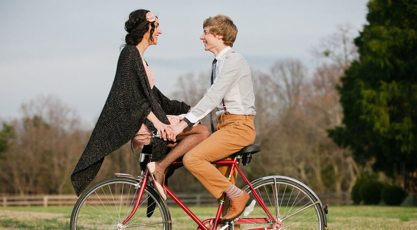 couple riding on bike woman sitting on handle bars in vintage-inspired attire