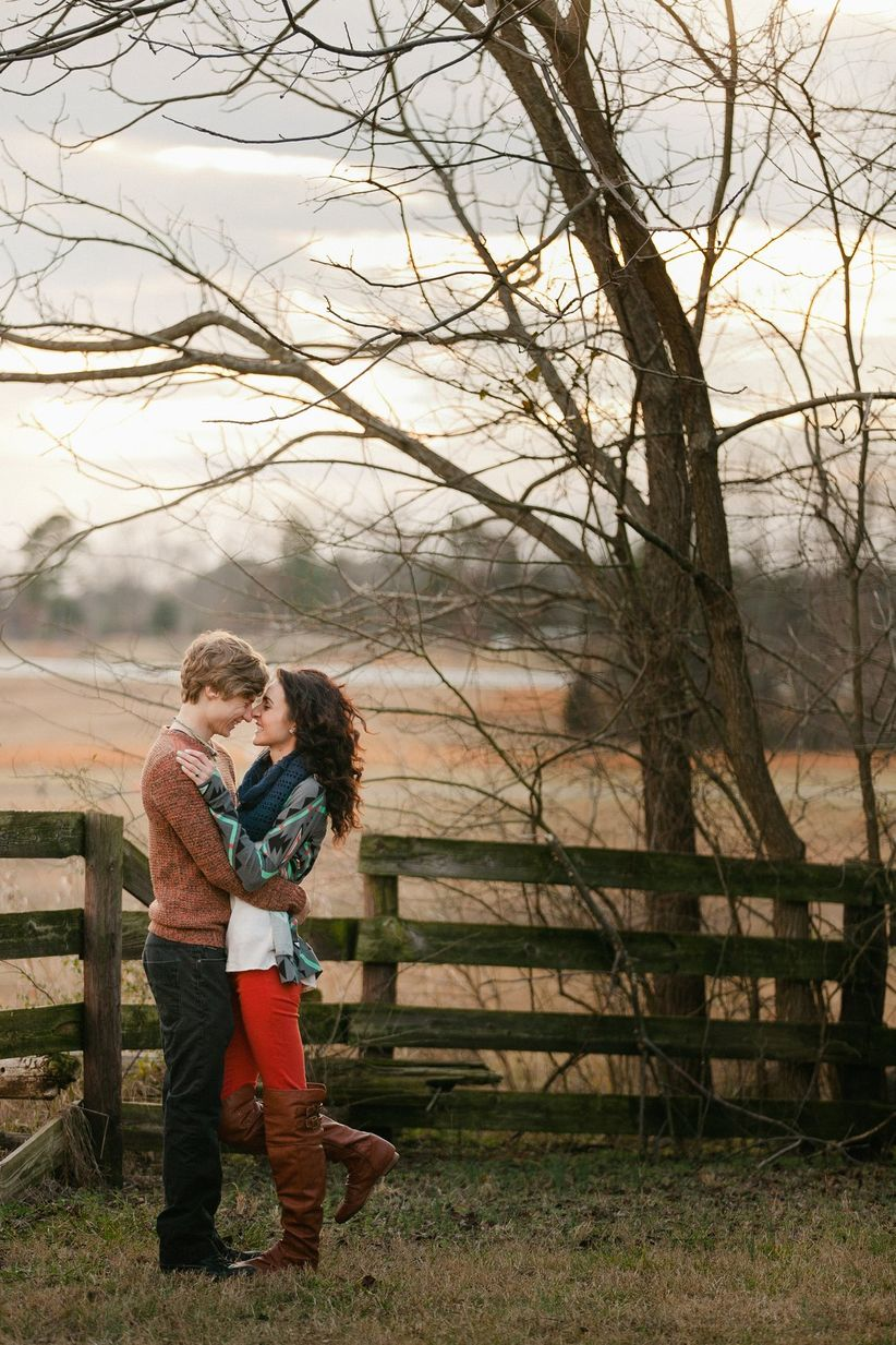 couple hugging next to wooden fence and a tree with no leaves
