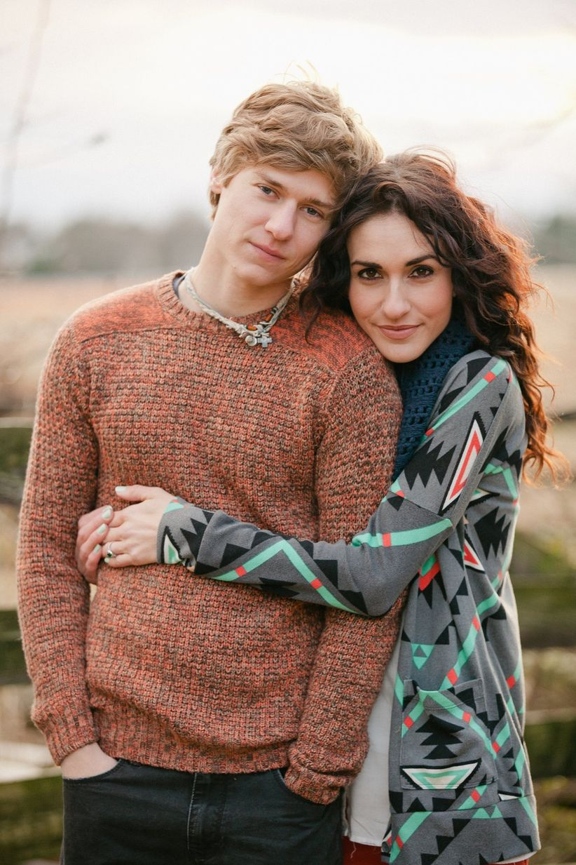 close up man and woman hugging looking at camera in casual attire