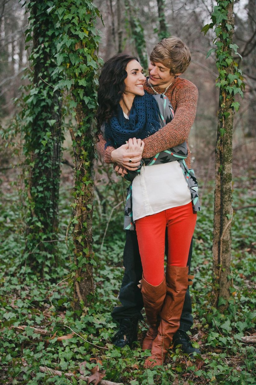 man hugging woman from behind in wooded area