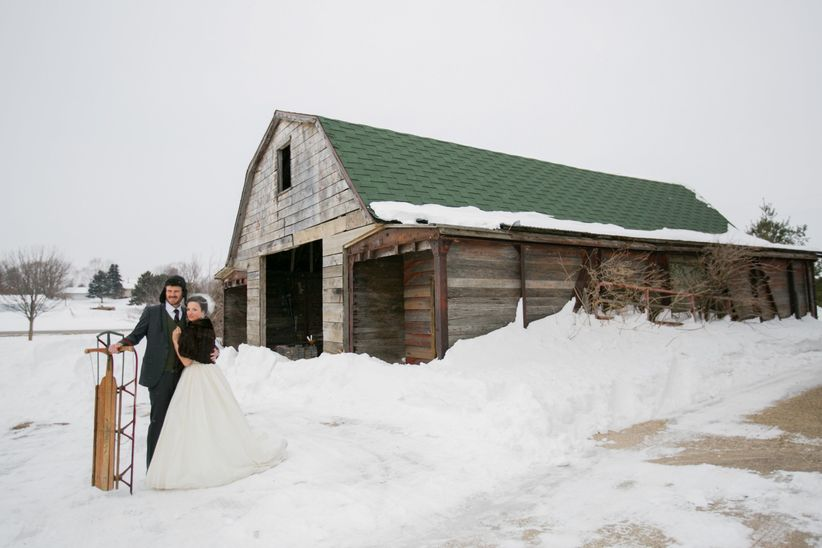 couple standing outside barn with sled
