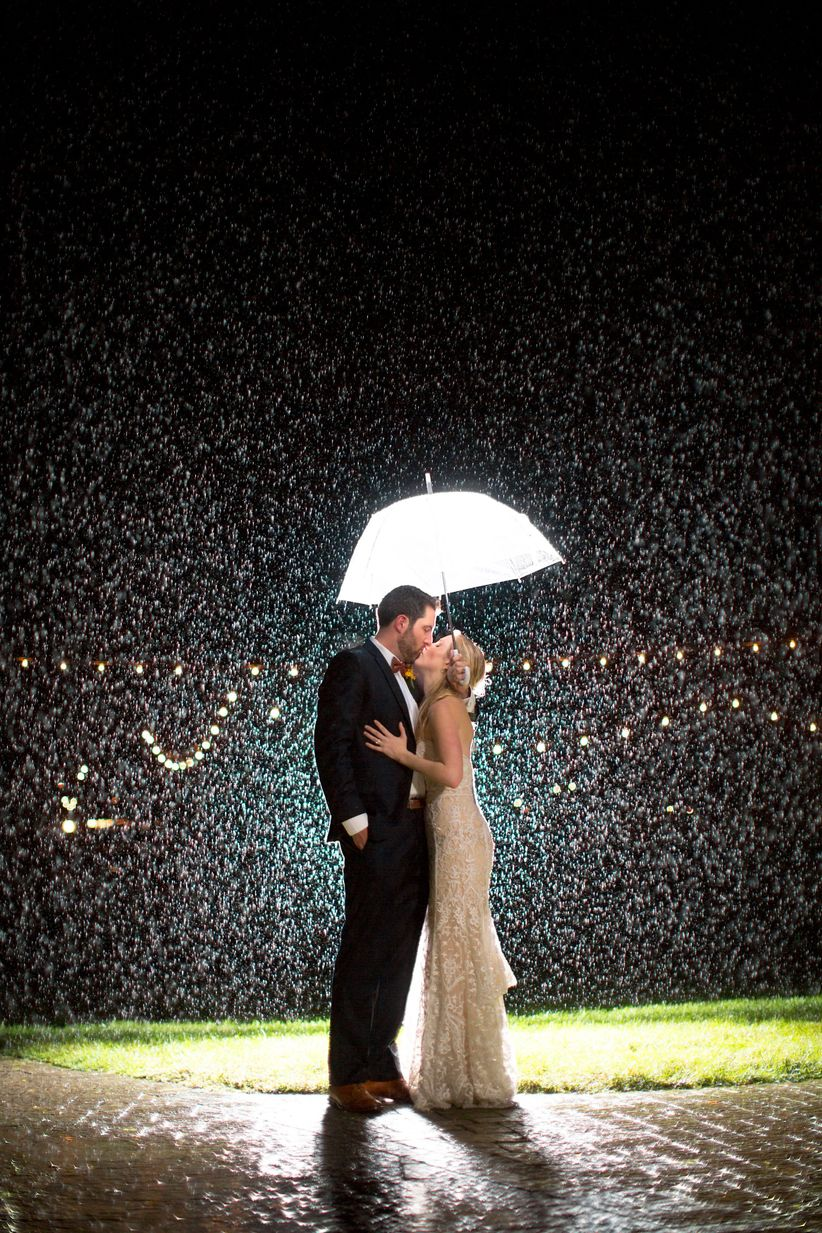 bride and groom kiss under umbrella at night