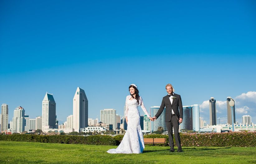 wedding couple holding hands and overlooking san diego