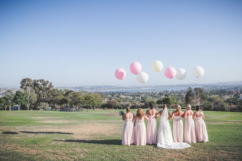 bridal party wearing pink dresses holding balloons and overlooking the city of san diego