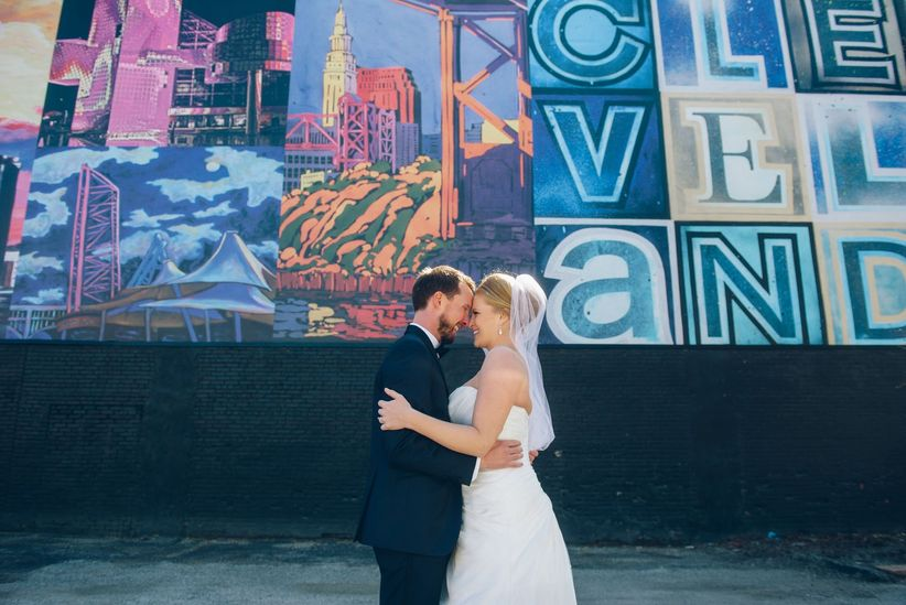 bride and groom pose with their wedding party in front of cleveland mural wall
