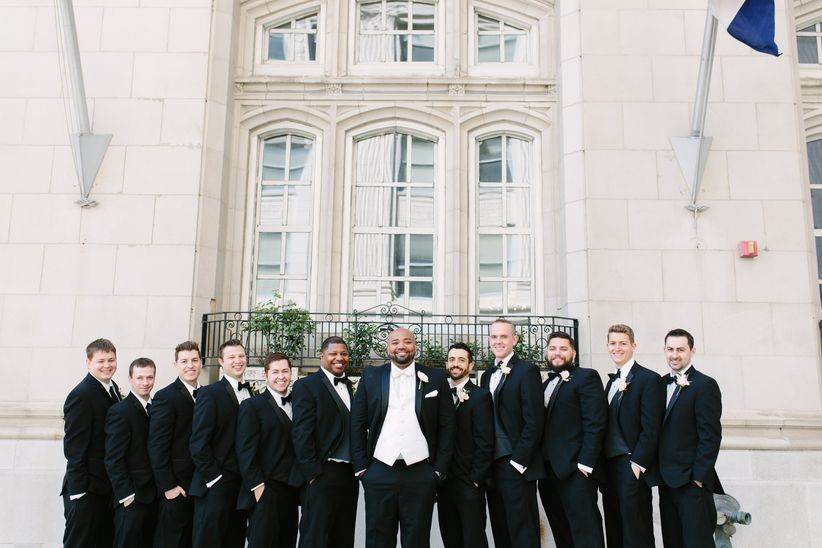 Renting vs buying your wedding tuxedo weddingwire groom and groomsmen black tuxedos outdoor junglespirit Image collections