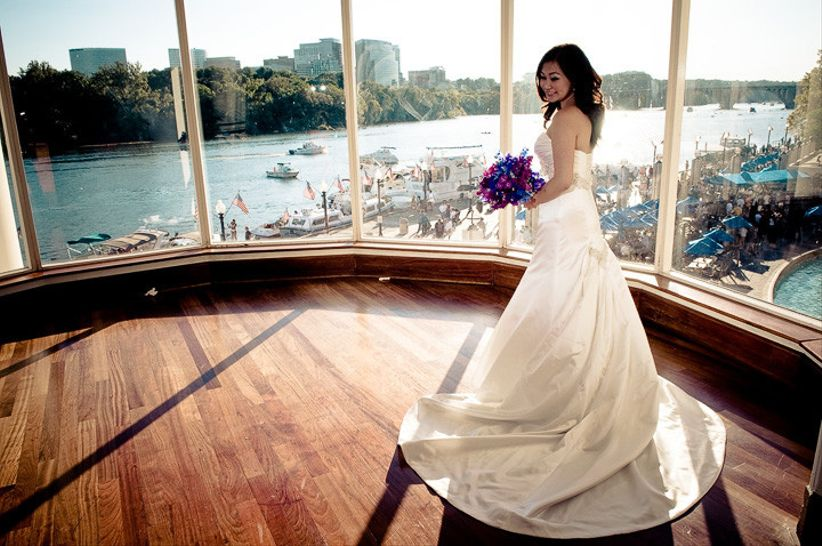 bride in a wedding dress stands near a window at Sequoia Restaurant in Georgetown overlooking the Potomac River