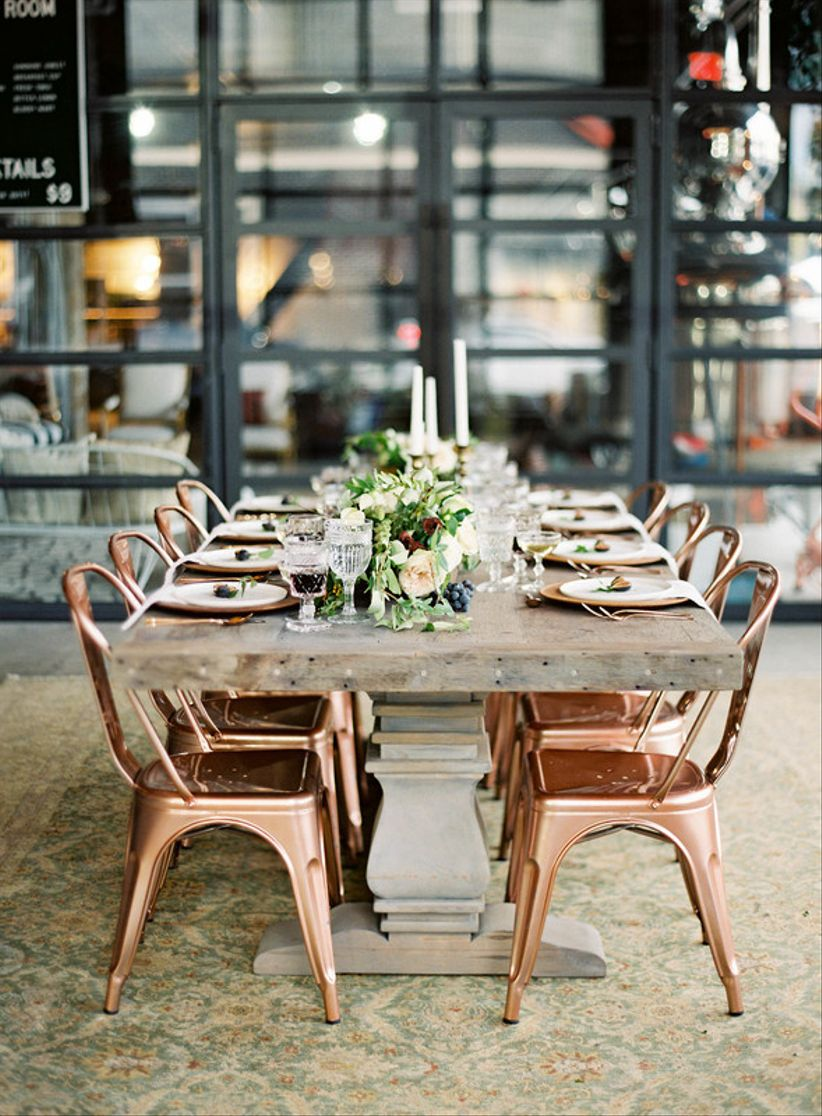 mid century modern wedding reception table with copper marais chairs and low centerpieces