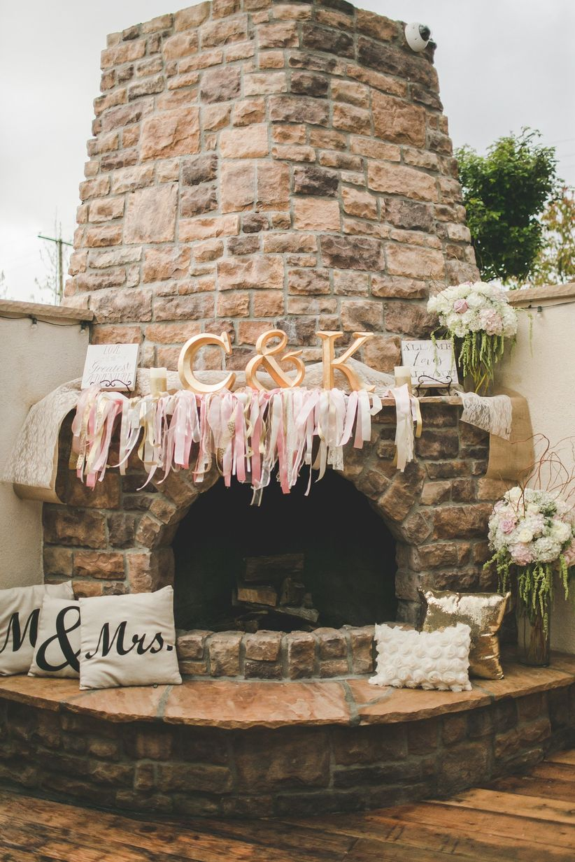 wedding venue with outdoor stone fireplace decorated with blush fabric streamers and gold monogram letters