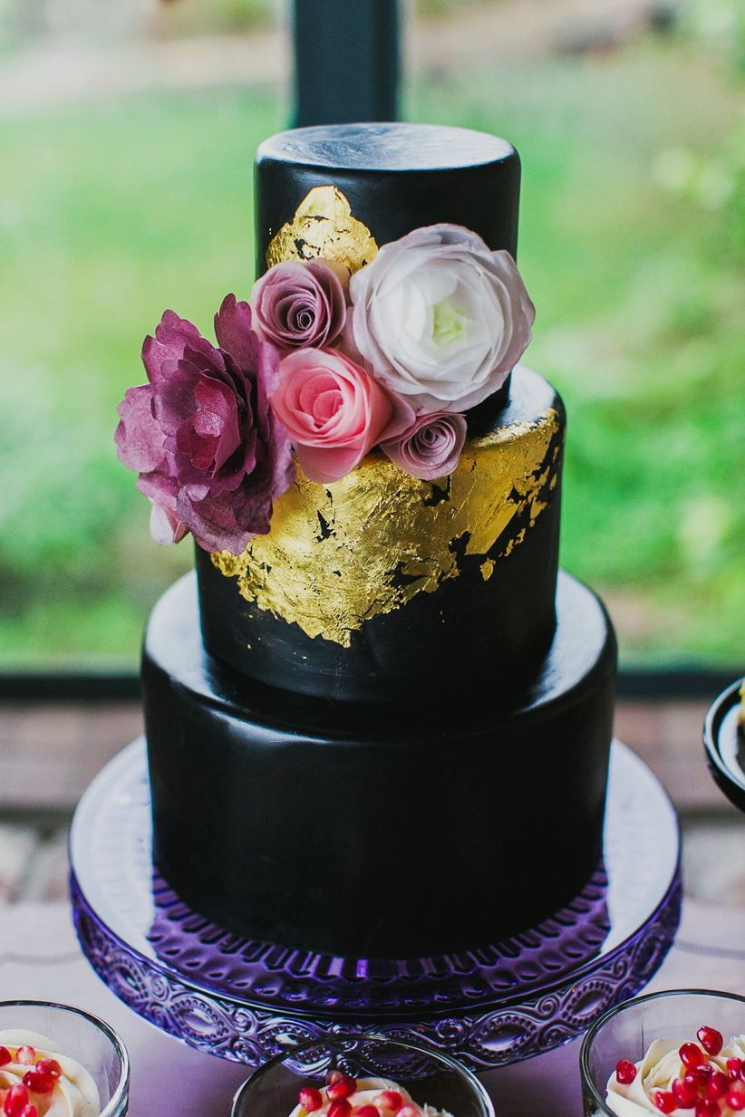 close up black fondant cake with gold leaf and floral topper