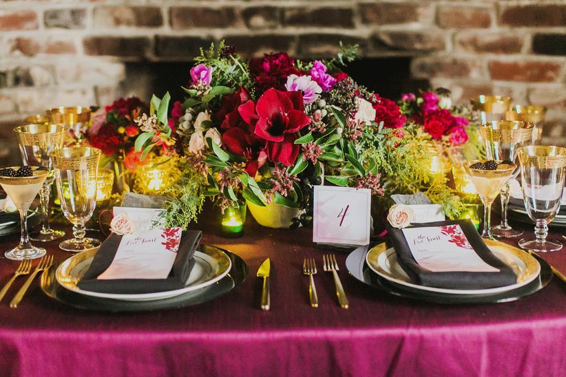 close up on two place settings large floral centerpiece red white pink black