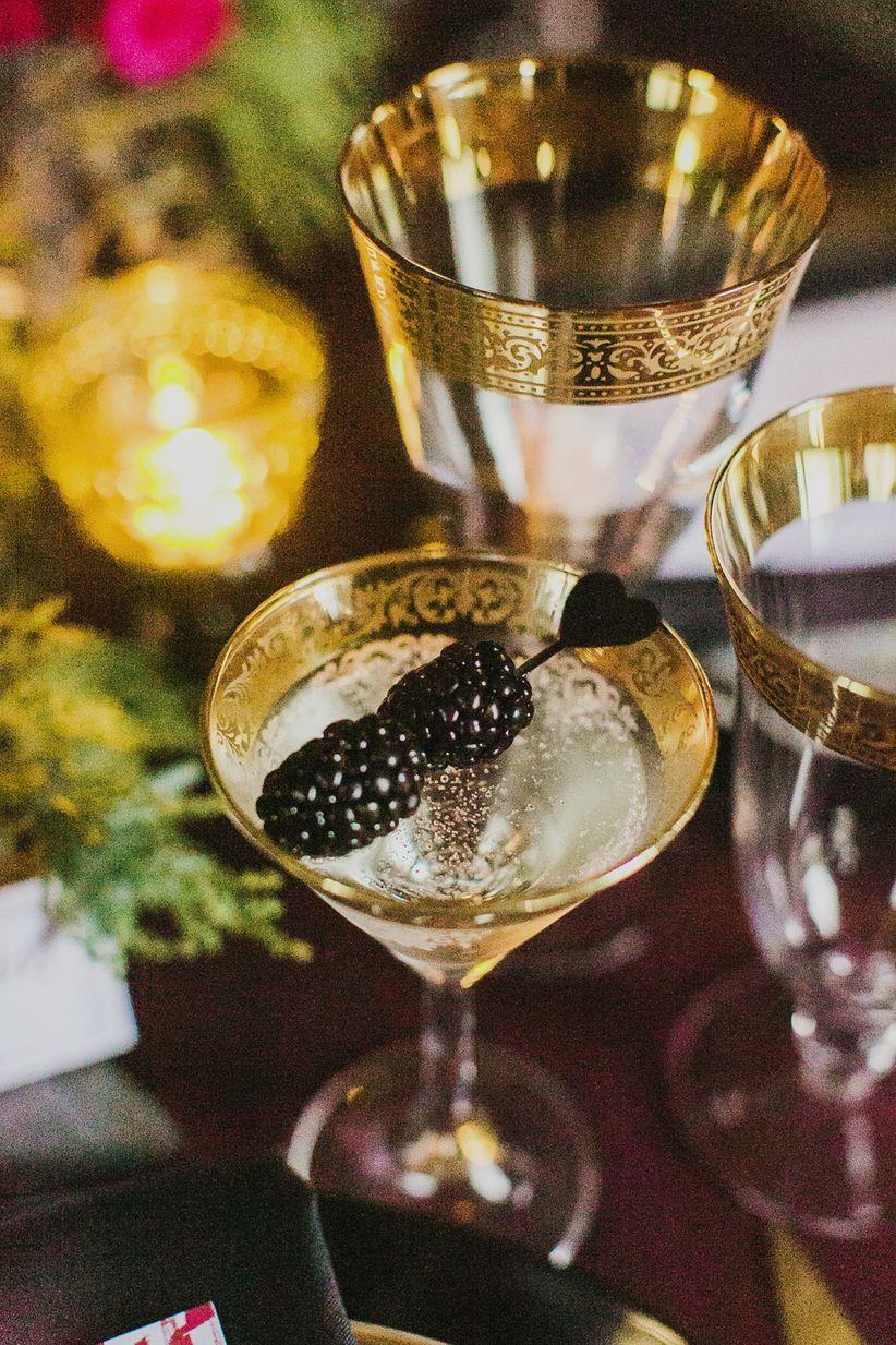 close upgold rimmed martini glass black stirrer with blackberries