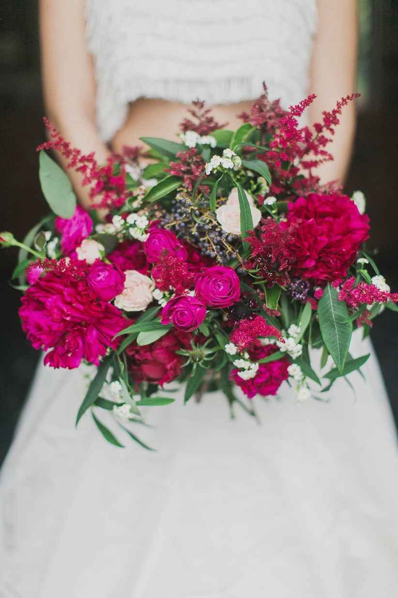 close up bridal bouquet with peonies ranunculus astilbe and viburnum berries