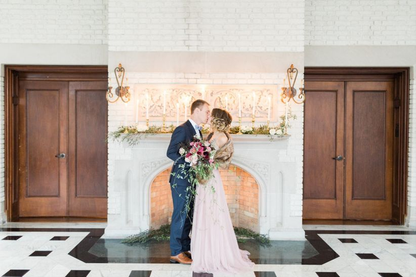 bride and groom kiss at elegant indoor wedding venue in front of white brick fireplace and mantel decorated with tall taper candles