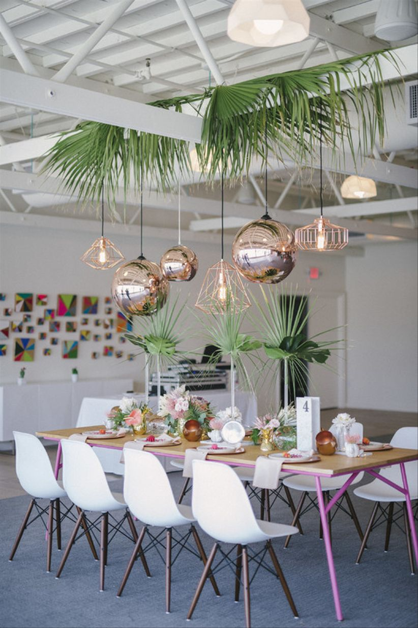 colorful Palm Springs wedding idea —modern wood table with bright pink and green centerpieces and geometric copper lighting fixtures