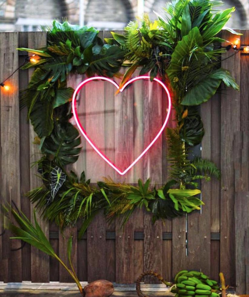 The 2018 wedding decor trends youre about to see everywhere modern wedding decor idea with pink neon heart sign surrounded by greenery junglespirit Gallery