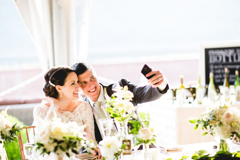 couple taking selfie at wedding reception