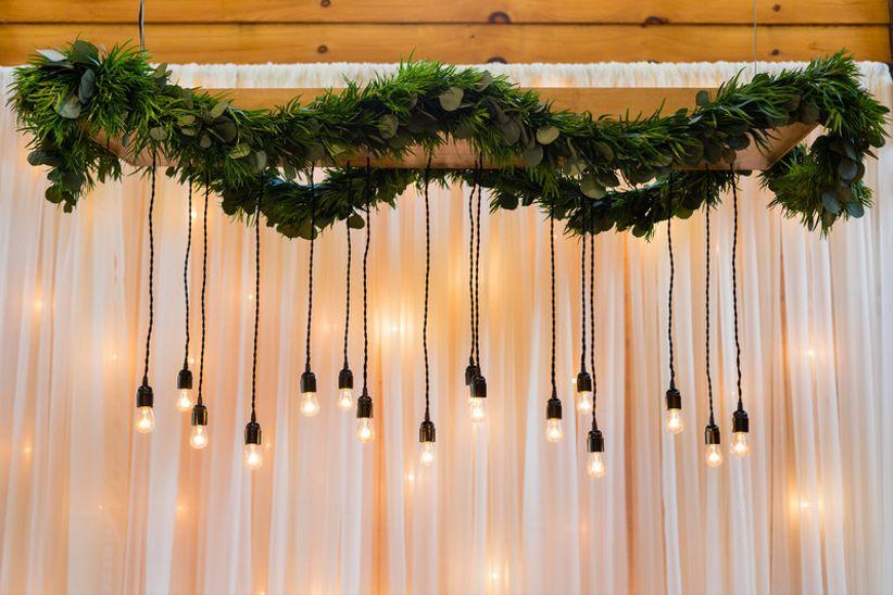 modern wedding idea —edison light bulbs and greenery above main table at reception