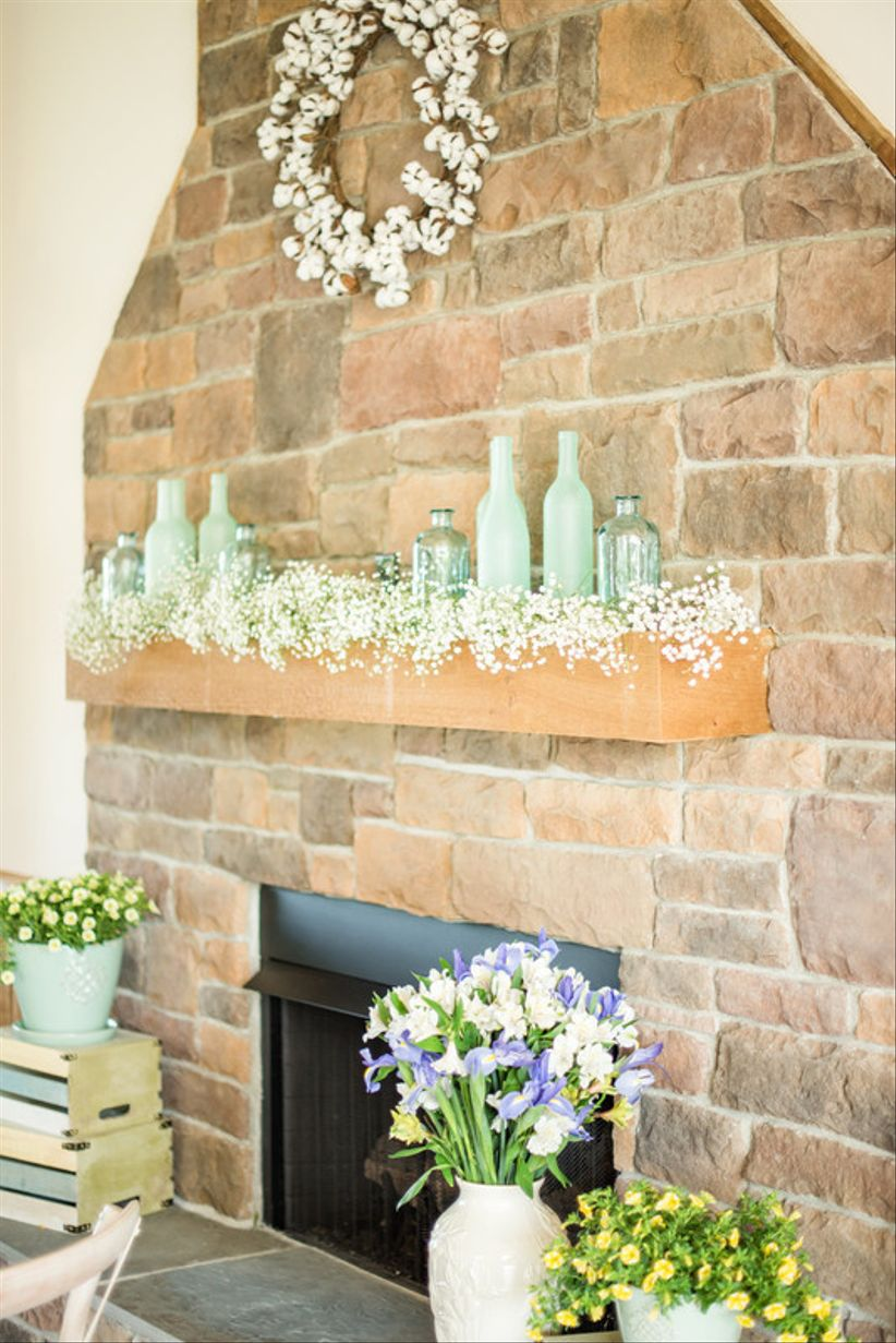 Stone fireplace mantel decorated with turquoise glass vintage bottles and baby
