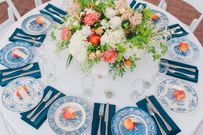 nautical preppy wedding tablescape with orange and pink centerpiece and vintage blue china