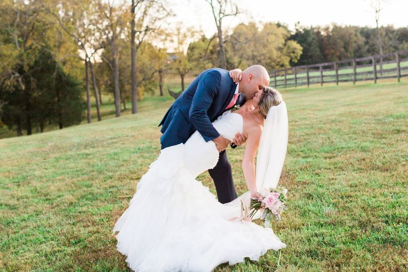 groom dipping bride while kissing outdoors