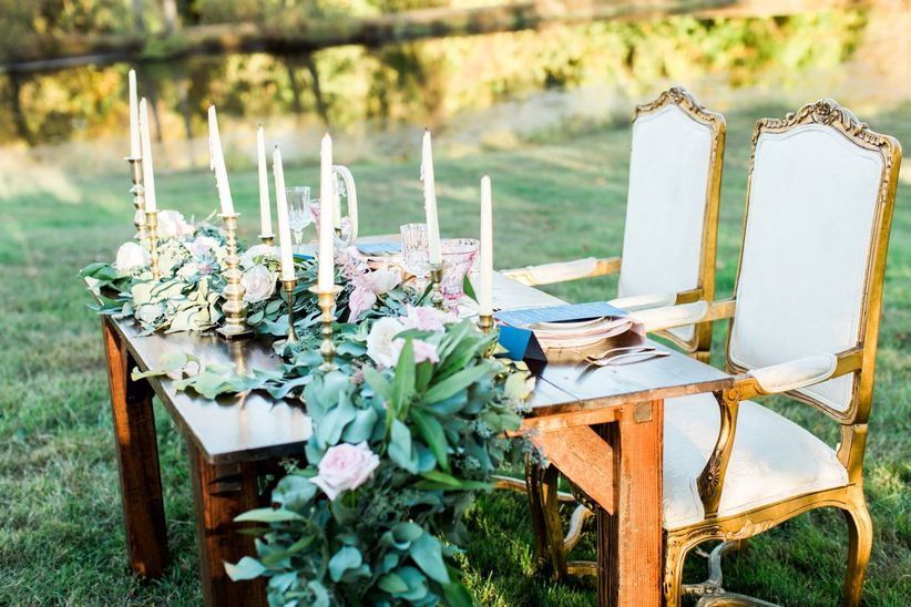 vintage sweetheart farmhouse table with greenery runner place setting and candles