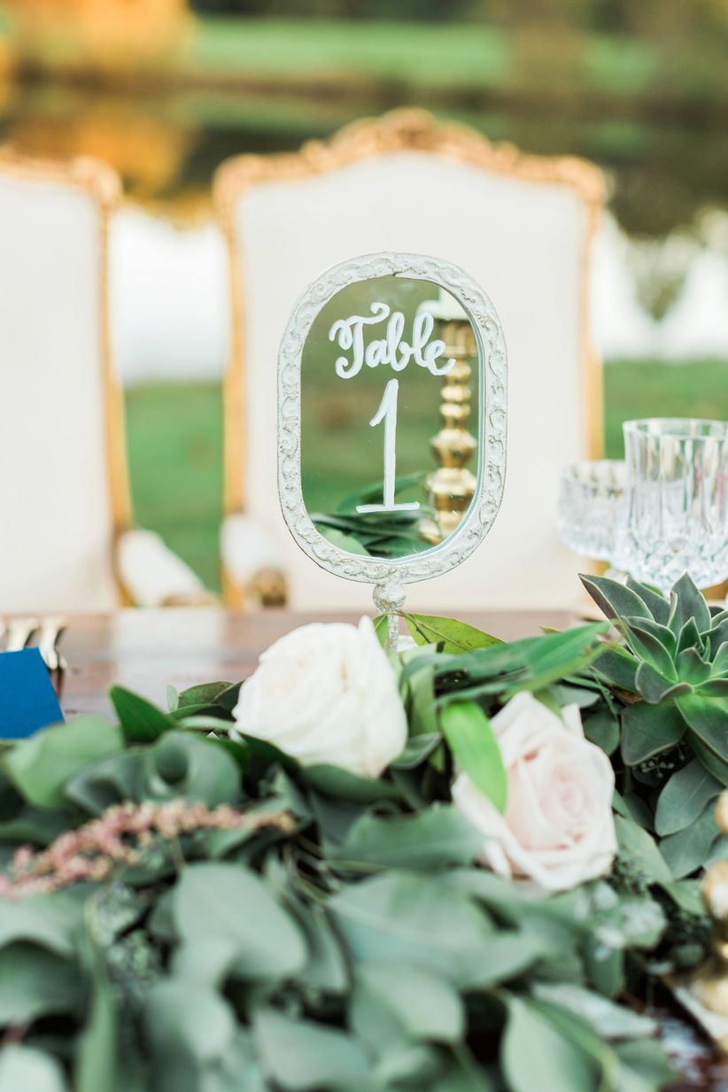 Table number handwritten on vintage mirror displayed on outdoor farmhouse table