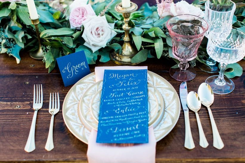close up vintage place setting handwritten menu card greenery runner