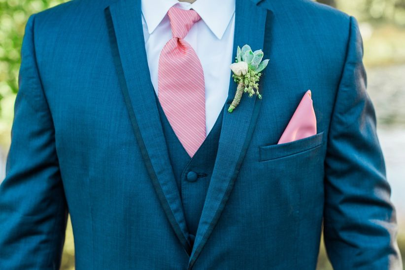 close up groom blue three piece suit pink tie floral boutonniere