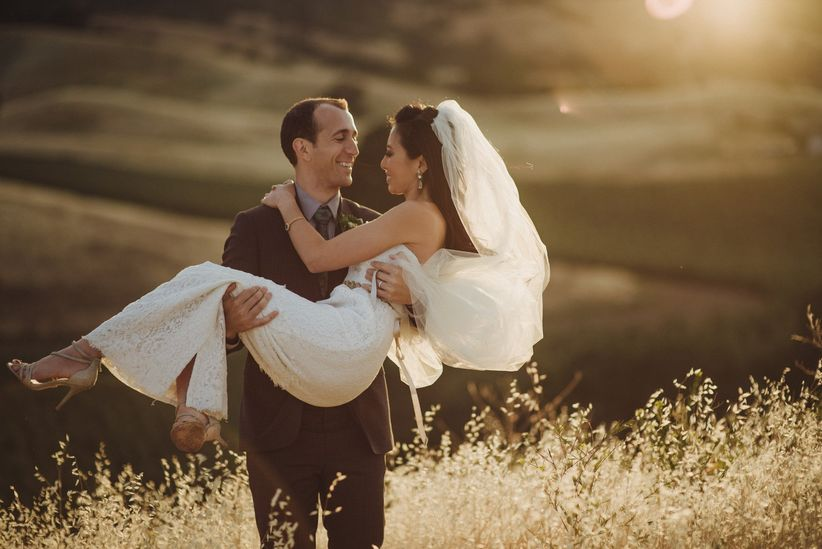 bride and groom pose on a hill at sunset