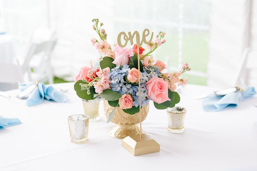 pink and blue floral centerpiece with calligraphed table number