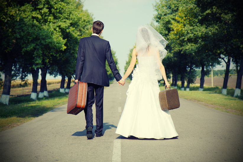 bride and groom with suitcases