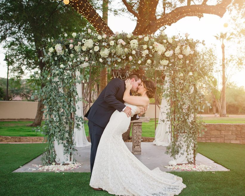 couple kissing in front of ceremony altar