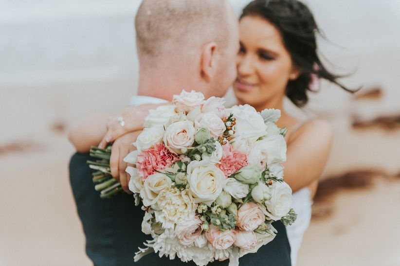 bride holding pink and green bouquet