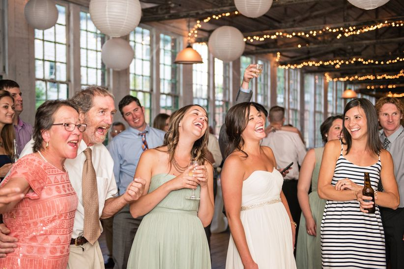 happy bride and guests on dance floor at reception