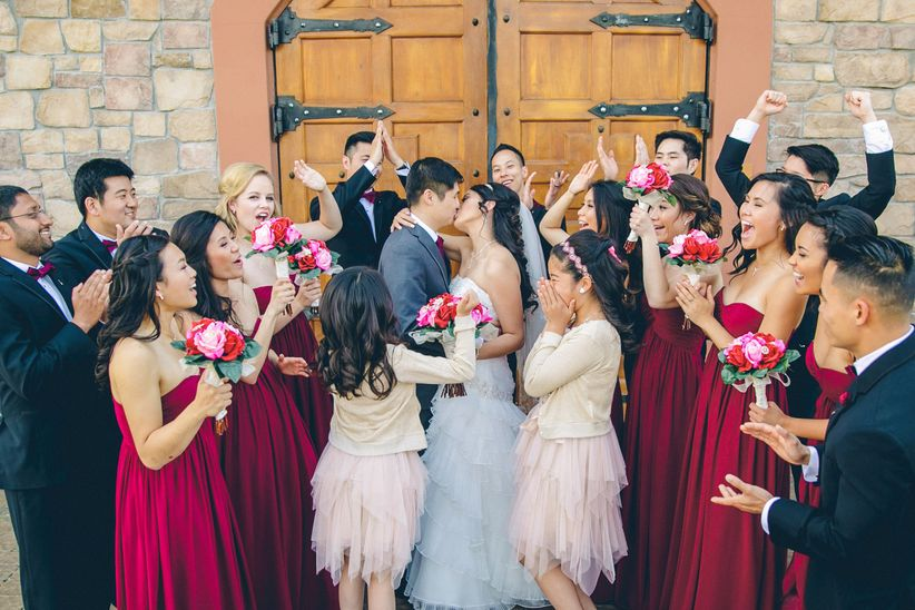 couple kissing surrounded by wedding party