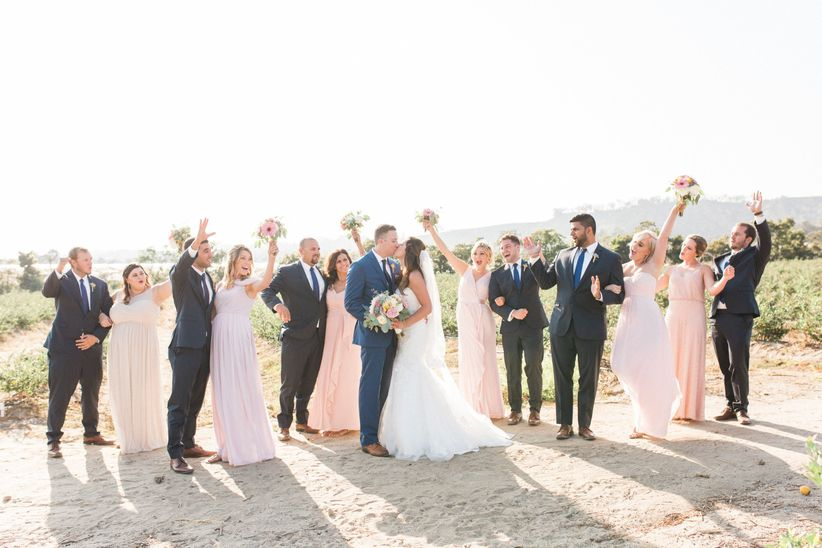 wedding party cheering on a beach while couple kisses