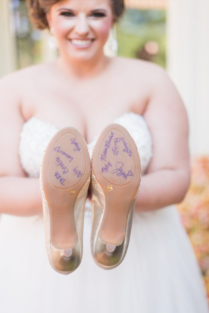 bridesmaid signing soles of brides shoes