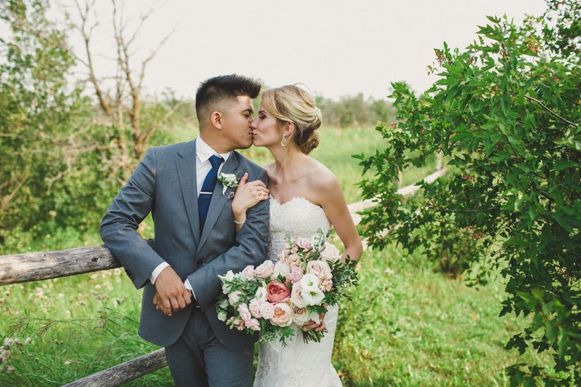 kissing wedding couple outdoors