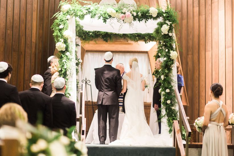 Jewish ceremony couple under chuppah with flowers and greenery
