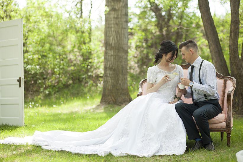 bride and groom drinking tea in woods on vintage love seat