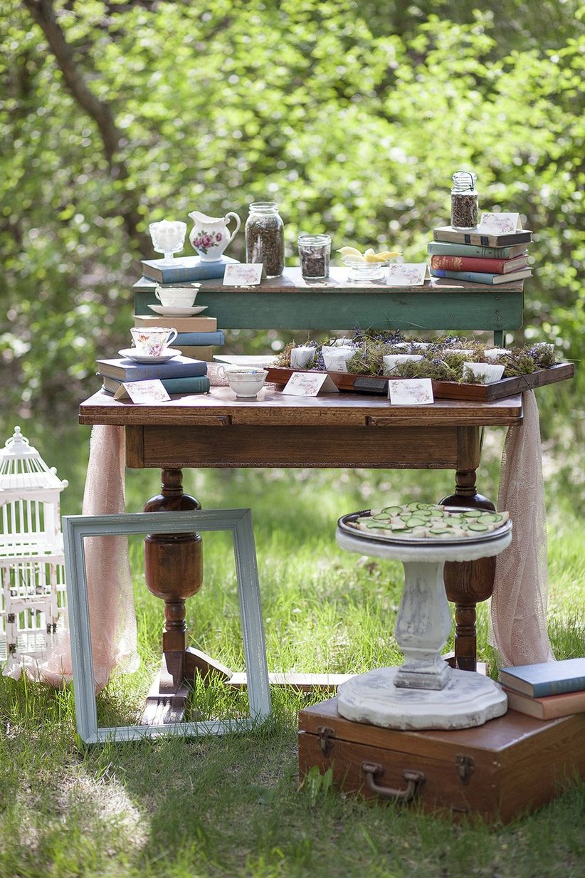 vintage-inspired outdoor tablescape decorated with a suitcase picture frame bide cage and classic books