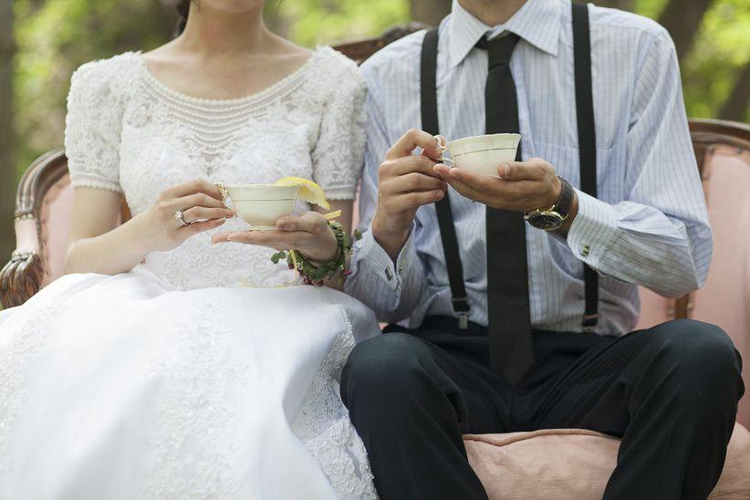 bride and groom sit on vintage love seat holding vintage tea cups