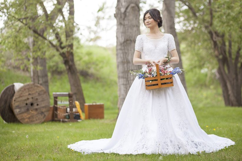 bride in lace ballgown holding basket of flowers