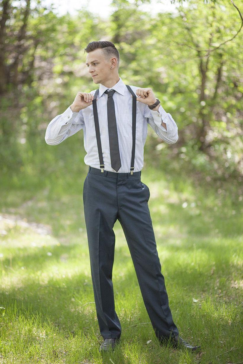 groom in field wearing slacks suspenders button down and a tie