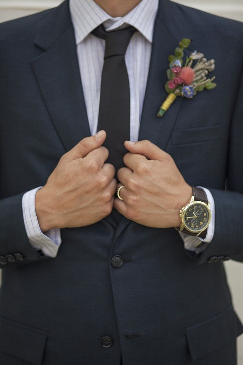 close up groom in dark blue suit with floral boutonniere striped button down and gray necktie