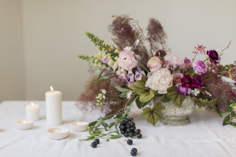 bohemian wedding centerpiece with purple flowers and greenery