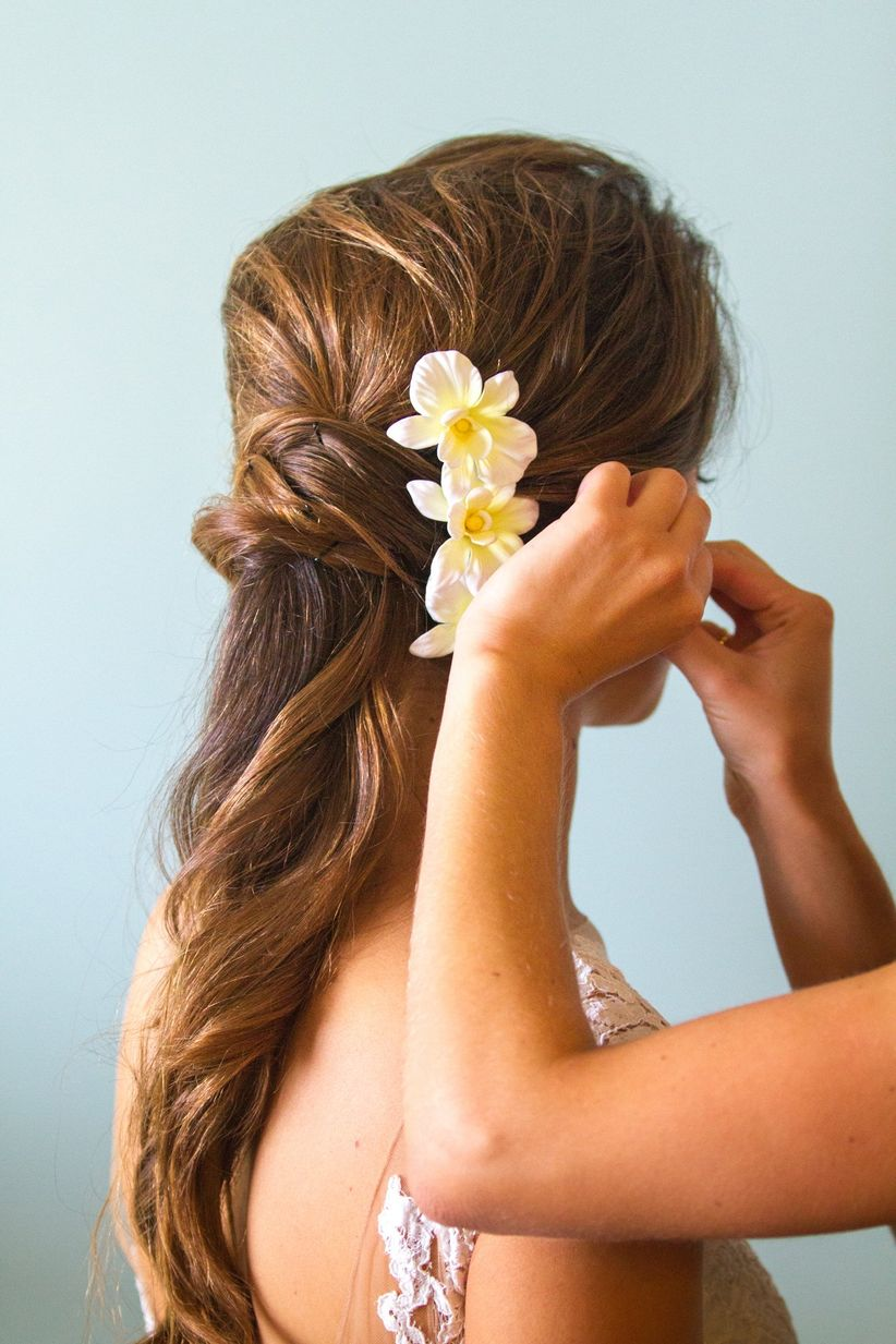 bridal hairstyle half up with flower accessory