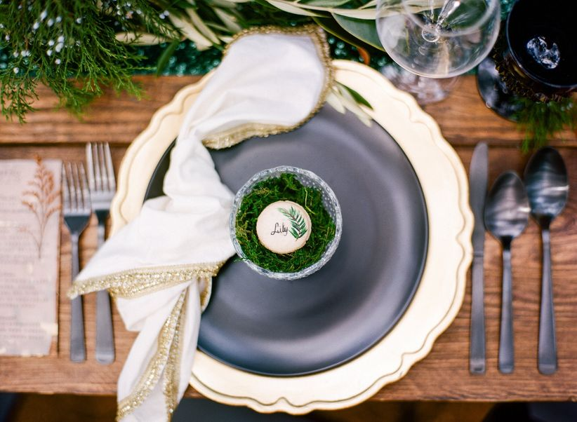 fairy themed wedding place setting with hand-painted macaron atop a bed of dried moss