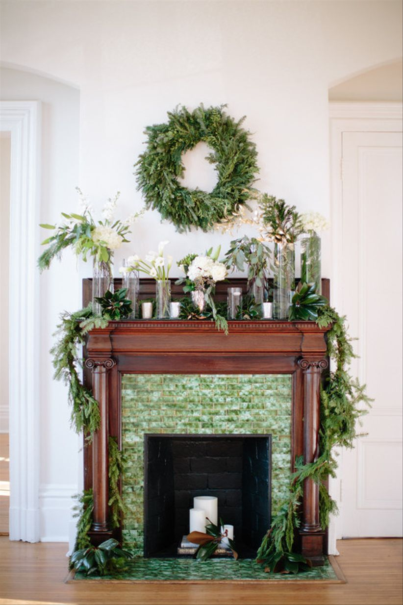 Dark wood fireplace mantel decorated with evergreen garland and greenery wreath with white candles